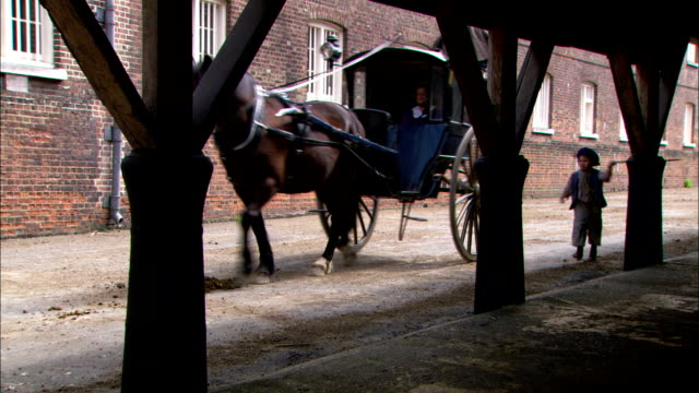 a young boy runs alongside a carriage in 19th-century london. - carriage stock videos & royalty-free footage