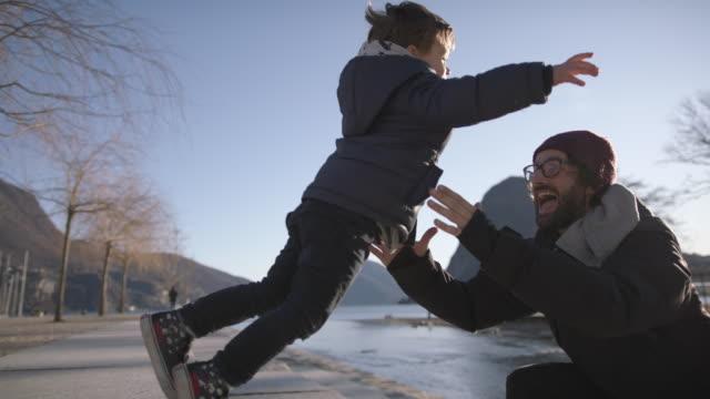 junge läuft und springt in väter arme bei sonnenuntergang am see - umarmen stock-videos und b-roll-filmmaterial