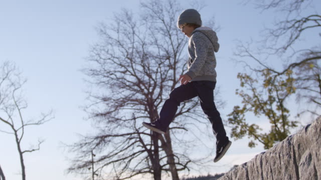 vidéos et rushes de young boy runs and jumps off stone wall in slow motion - 8 9 ans