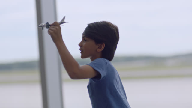 SLO MO. Young boy runs and plays with toy airplane in front of gate window in airport terminal.