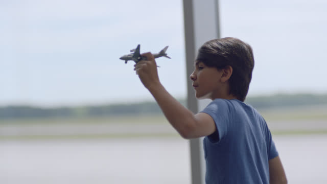 slo mo. young boy runs and plays with toy airplane in front of gate window in airport terminal. - コンコース点の映像素材/bロール