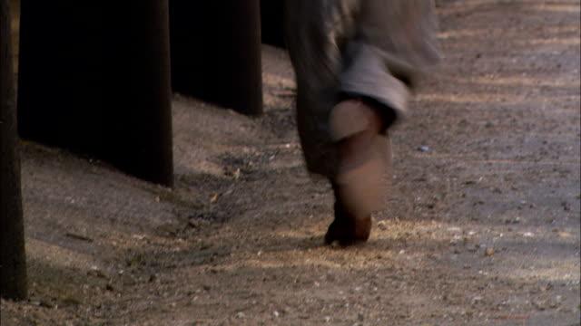 a young boy runs down a cobblestone street in 19th century london. - xix secolo video stock e b–roll