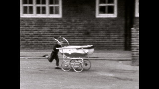 young boy runs fast pushing pram past houses; 1969 - old stock videos & royalty-free footage