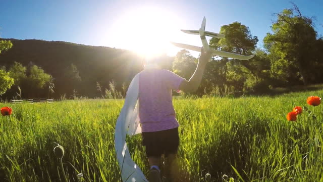Young Boy Runs through Field Flying Airplane