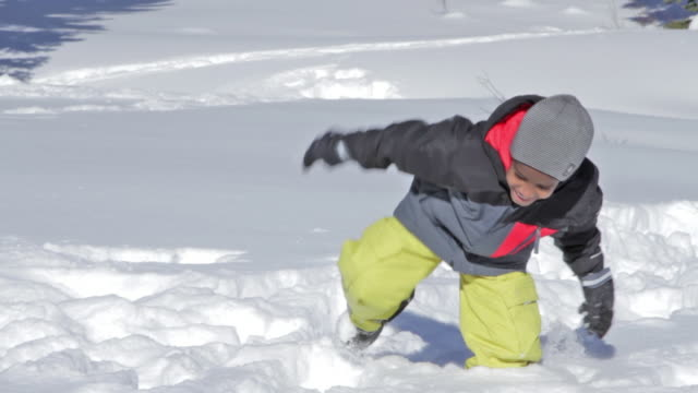 stockvideo's en b-roll-footage met a young boy runs through the snow on a sunny, winter day - alleen jongens