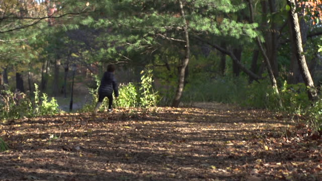 Young boy runs with a stick down a path to and from camera