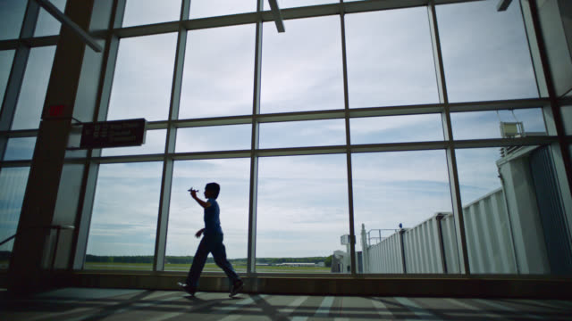 SLO MO. Young boy runs with toy airplane near gate window in airport terminal. Pull back.