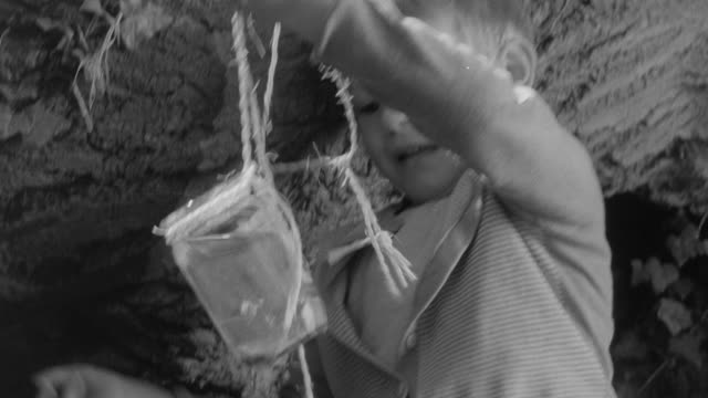 1960 montage young boy scooping river water with a jar and string in nursery school / united kingdom - riverbank stock videos and b-roll footage