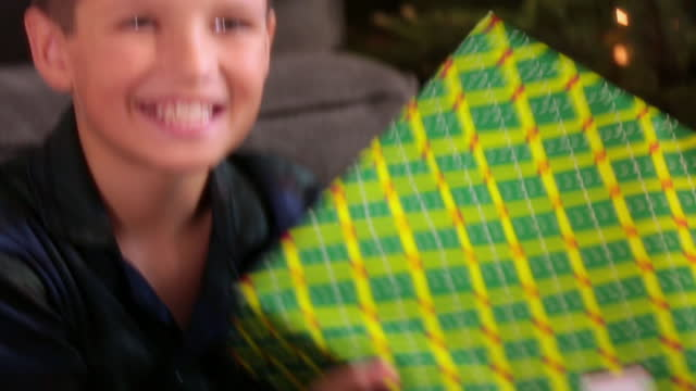 Young boy shakes Christmas present excitedly for camera