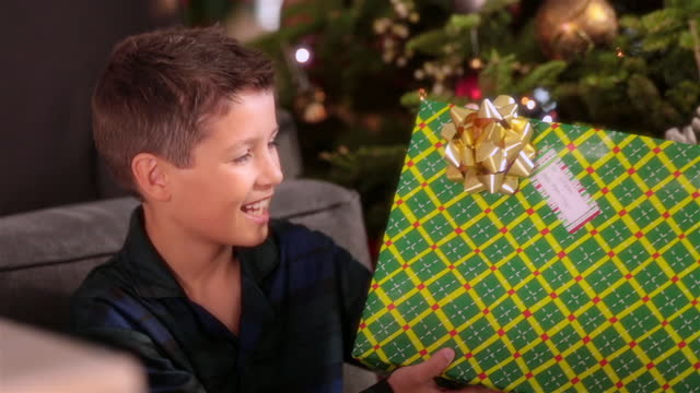 Young boy shakes present excitedly in front of Christmas tree
