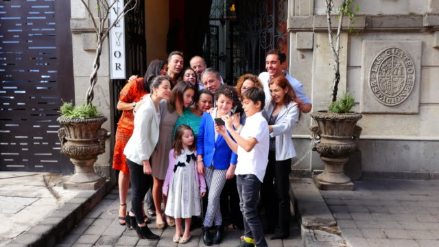 MS TU SWISH PAN Young boy showing photo on smartphone to smiling multigenerational family in front of restaurant entrance