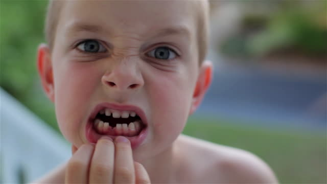 vidéos et rushes de a young boy shows his missing front tooth excitedly (close-up) - fierté