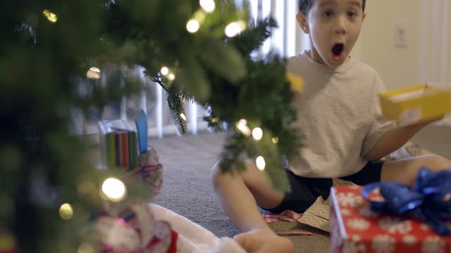 young boy shows surprise when he opens and empty box at christmas - christmas gift stock videos & royalty-free footage