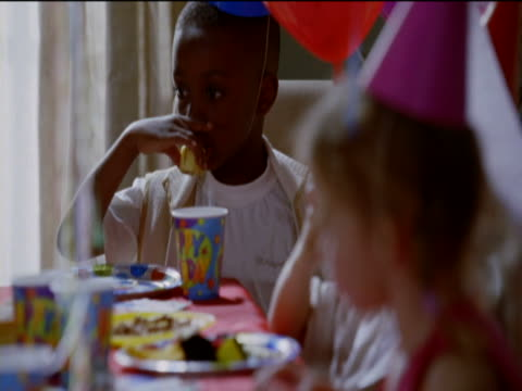 young boy sits at a table eating cake from a disposable plate at a birthday party - female with group of males stock videos and b-roll footage