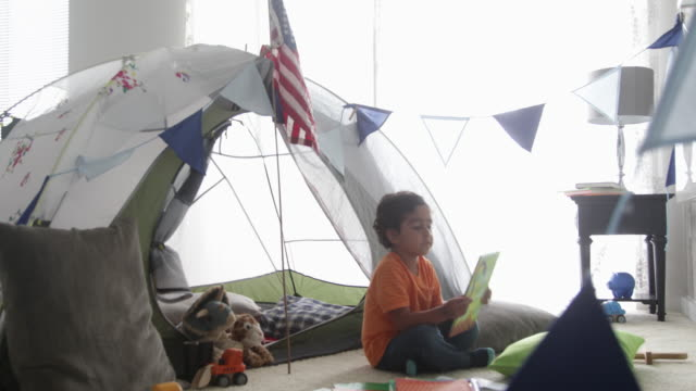 pan young boy sits down with a book in front of play tent. - pillow stock videos & royalty-free footage