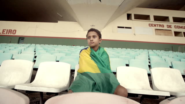 young boy sits in empty soccer stadium wrapped in brazilian national flag - international soccer event stock videos & royalty-free footage