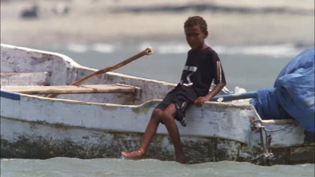 a young boy sits on the edge of a rowboat. - yemen bildbanksvideor och videomaterial från bakom kulisserna