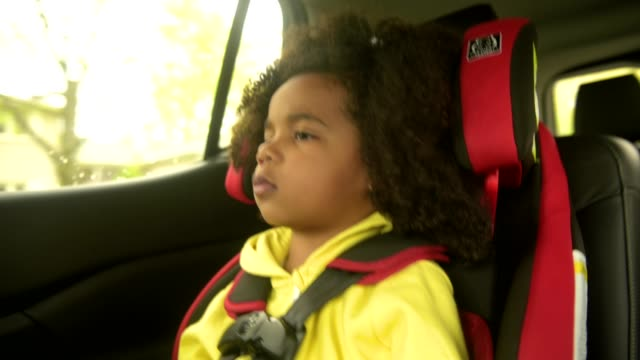 young boy sitting in car seat in vehicle. - beifahrersitz oder rücksitz stock-videos und b-roll-filmmaterial