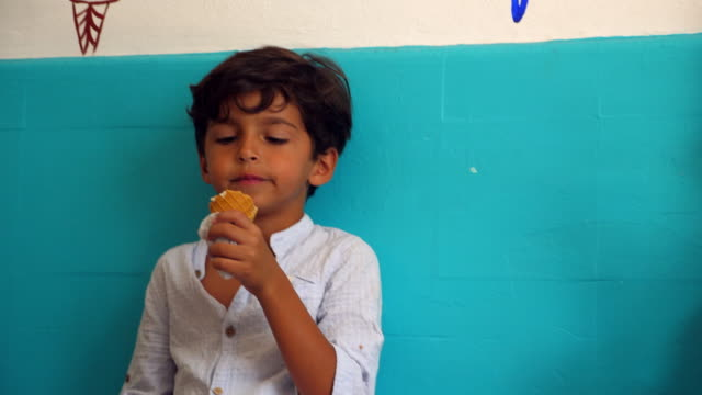 ms young boy sitting in ice cream shop enjoying ice cream - pampering stock videos & royalty-free footage