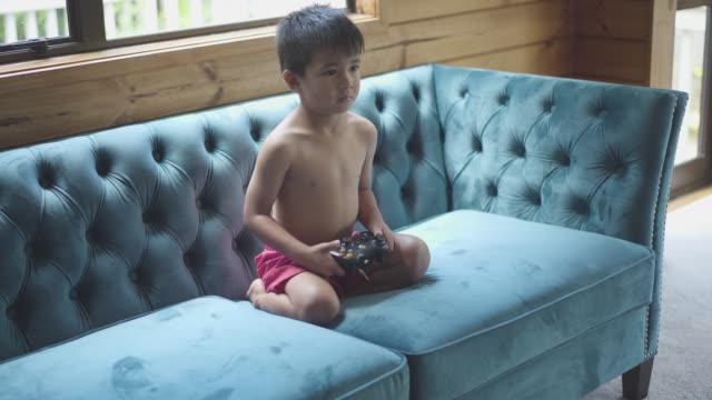 Young boy sitting on sofa busy playing video games.