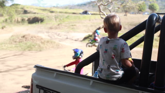 vídeos de stock e filmes b-roll de young boy sitting on the back of a pickup truck watching motocross - kelly mason videos