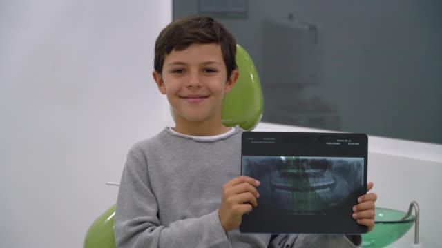 vídeos y material grabado en eventos de stock de joven sentado en la silla del dentista sosteniendo una radiografía mientras sonríe a la cámara - dentista