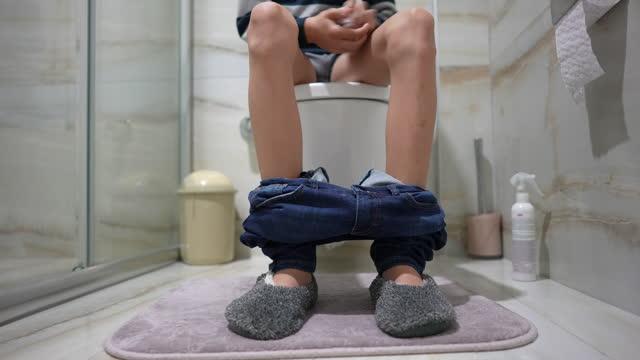 junge sitzt auf dem toilettensitz - sitzen stock-videos und b-roll-filmmaterial