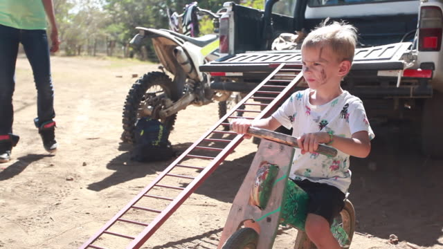 vídeos y material grabado en eventos de stock de young boy sitting on wooden bike behind pickup truck while a mom walks around him and another young boy gets into the pickup truck - kelly mason videos