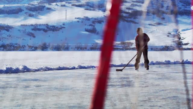 Young boy skating towards a hockey goal.