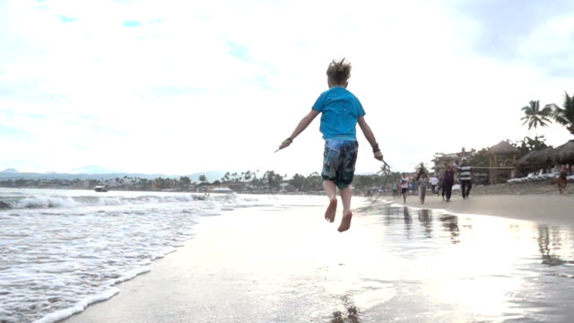 young boy skips in shallows on the beach - skipping along stock videos & royalty-free footage