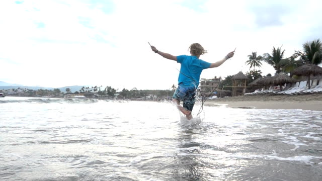 young boy skips in shallows on the beach - shorts stock videos & royalty-free footage