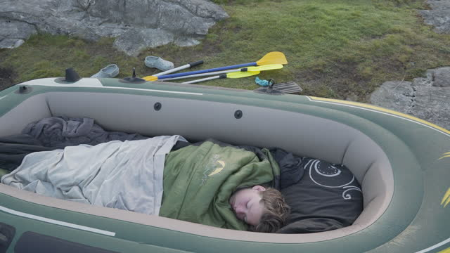a young boy sleeping in his dingy at wastwater lake, cumbria, uk - 寝袋点の映像素材/bロール