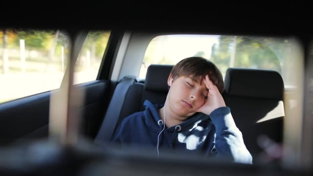 young boy sleeps in a car without seat belt - teenage boys stock videos & royalty-free footage