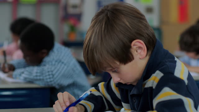a young boy sleeps in class until his classmate wakes him up. - aula video stock e b–roll