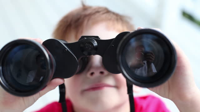 stockvideo's en b-roll-footage met a young boy smiles, then looks through binoculars. - nieuwsgierigheid