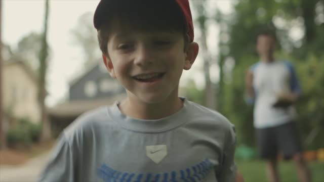 Young boy smiling and running tin backyard