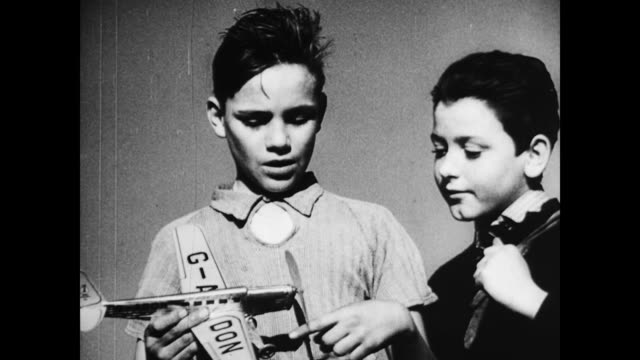 / young boy smiling as wind blows through his hair. boys playing with model airplane on january 01, 1939 - 1939 stock videos & royalty-free footage