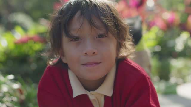 slo mo cu young boy softly smiles at camera - mixed race person stock videos & royalty-free footage