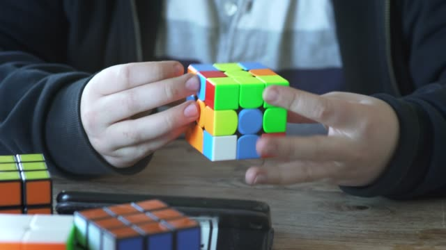 a young boy solving a cube puzzle in less than a minute. - solutions stock videos & royalty-free footage