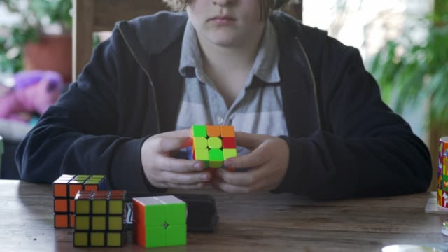 a young boy solving a cube puzzle in less than a minute. - formula video stock e b–roll