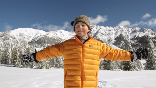 vídeos de stock e filmes b-roll de  ms tu slo mo young boy spinning and smiling at outdoors on beautiful winter's days / sun valley, idaho, united states - braço humano