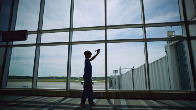 SLO MO. Young boy spins and plays with toy airplane near gate window in airport terminal. Push in.