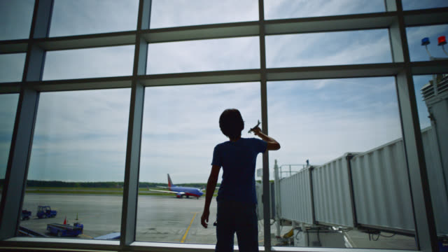 SLO MO. Young boy spins and plays with toy airplane near gate window in airport terminal. Pull back.