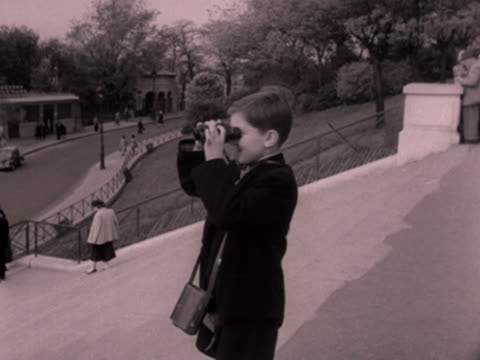 young boy standing in front of the sacre coeur uses binoculars to look at the city. the camera pans left across the skyline of paris. 1952. - binoculars stock videos & royalty-free footage