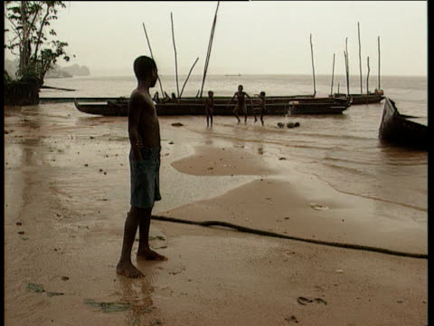young boy stands alone in foreground while others splash in river by boats french guiana - french guiana stock videos & royalty-free footage