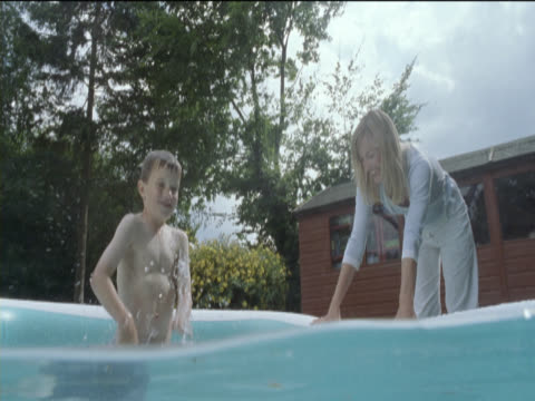 vidéos et rushes de young boy stands splashing the water in a paddling pool with his mother standing next to the pool - pataugeoire