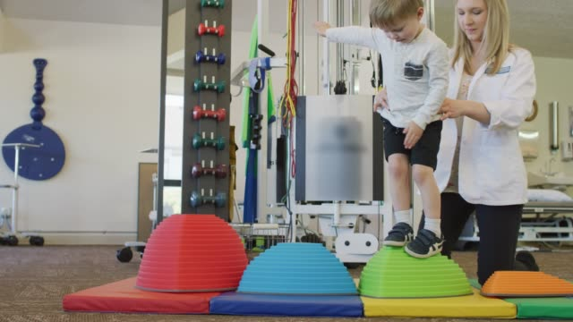 young boy steps from object to object - physical therapist stock videos & royalty-free footage