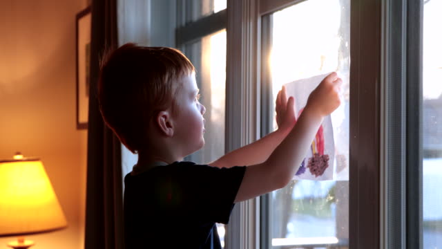 young boy sticking his rainbow drawing on home window during the covid-19 crisis at sunset - sharing stock videos & royalty-free footage