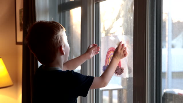 young boy sticking his rainbow drawing on home window during the covid-19 crisis at sunset - waving gesture stock videos & royalty-free footage