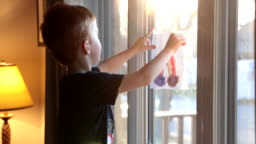Young Boy sticking his rainbow drawing on home window during the Covid-19 crisis at sunset